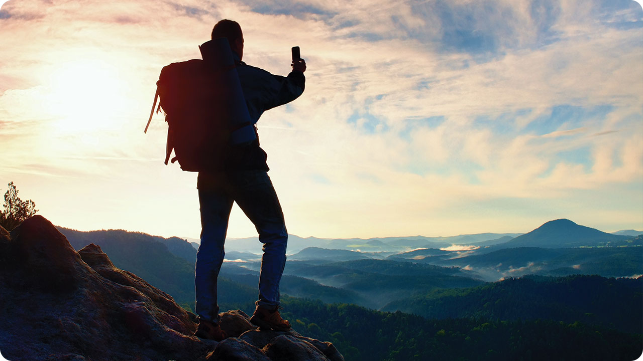 Man standing on a mountain top holding an outstretched phone